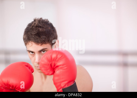 Portrait of young man in boxing gloves - Stock Photo