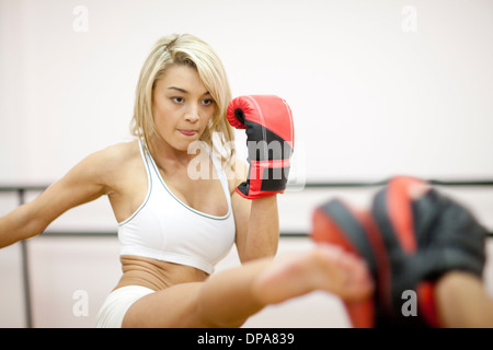 Young woman kickboxing in gym - Stock Photo
