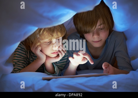 Brothers underneath duvet using digital tablet - Stock Photo