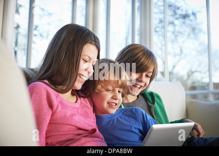 Siblings using digital tablet together - Stock Photo