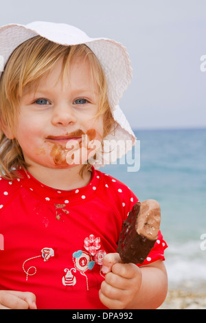 Baby girl eating ice cream on beach - Stock Photo