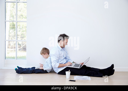 Father and son sitting back to back using laptop and digital tablet - Stock Photo