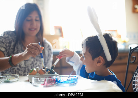 Woman and boy wearing bunny ears painting Easter eggs - Stock Photo
