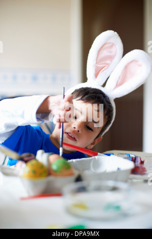 Boy wearing bunny ears painting Easter eggs - Stock Photo