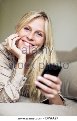 Woman holding mobile phone in bed - Stock Photo