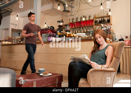 Young woman having tea and reading newspaper in cafe - Stock Photo