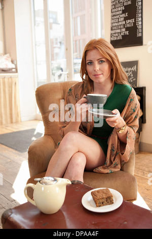 Portrait of young woman having tea and cake in cafe - Stock Photo