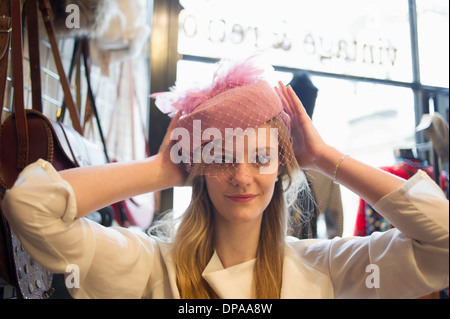 Woman trying on vintage hat - Stock Photo