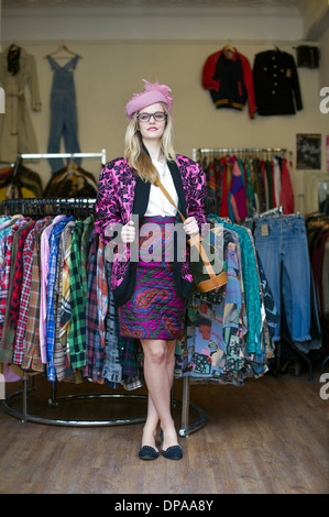 Woman standing in clothes shop wearing vintage clothes - Stock Photo