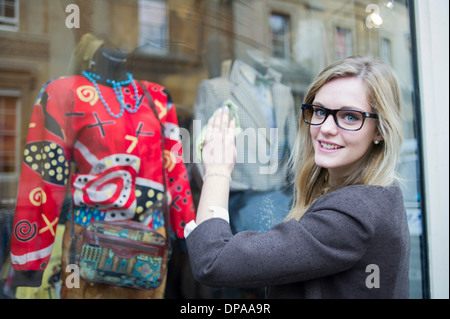 Woman cleaning window of clothes shop - Stock Photo