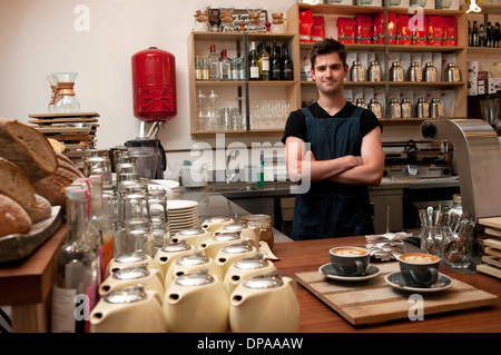 Portrait of young man behind kitchen counter in cafe - Stock Photo
