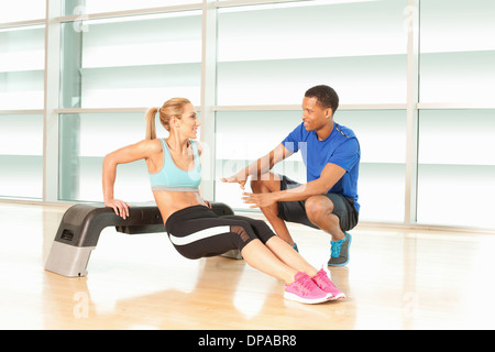 Woman doing exercise on step with man instructing - Stock Photo