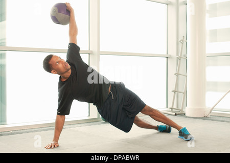 Man stretching using exercise ball - Stock Photo