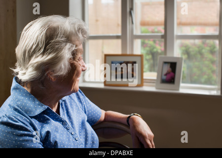 Senior adult woman sitting in room looking out of window - Stock Photo
