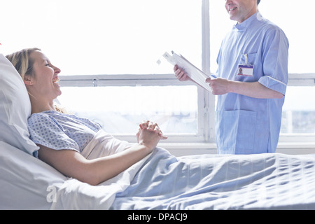 Patient lying in hospital bed laughing with nurse - Stock Photo