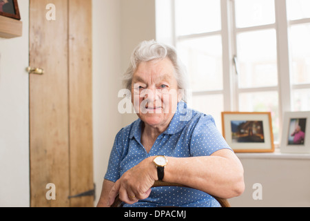 Senior adult woman sitting in room - Stock Photo