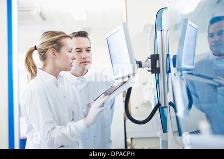 Researchers looking at computer in lab - Stock Photo