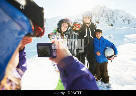 Girl photographing family, Les Arcs, Haute-Savoie, France - Stock Photo