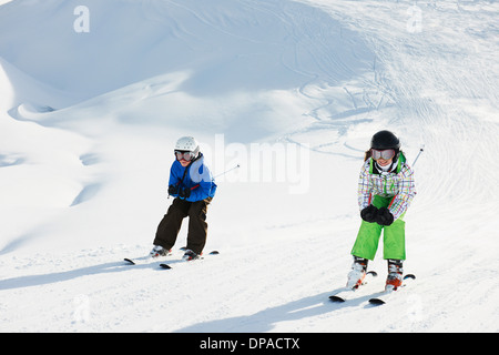 Brother and sister skiing, Les Arcs, Haute-Savoie, France - Stock Photo