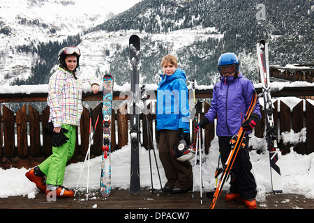 Portrait of brother and sisters holding skis