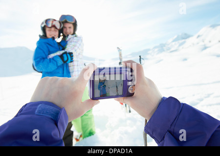 Sister photographing siblings in snow, Les Arcs, Haute-Savoie, France - Stock Photo