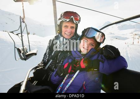 Portrait of grandmother and granddaughter on ski lift, Les Arcs, Haute-Savoie, France - Stock Photo