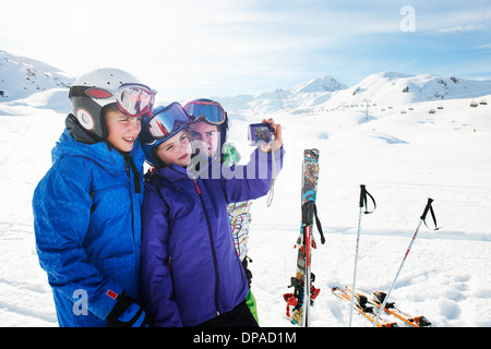 Brother and sisters taking self portrait, Les Arcs, Haute-Savoie, France - Stock Photo
