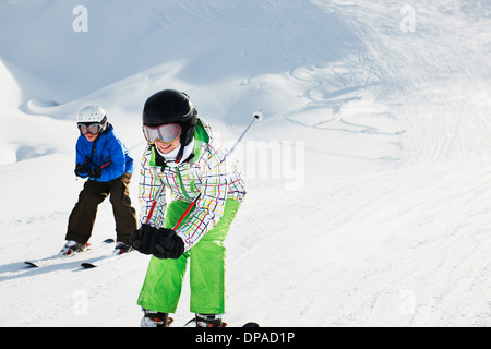 Brother and sister skiing downhill, Les Arcs, Haute-Savoie, France - Stock Photo