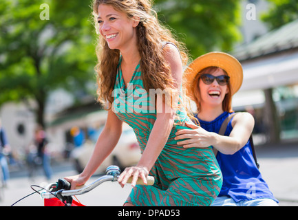 Two female friends riding bicycle - Stock Photo