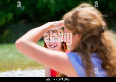 Two female friends in sunlight, one shielding eyes - Stock Photo
