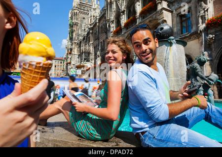 Couple and woman with ice cream, Munich Marienplatz, Munich, Germany - Stock Photo