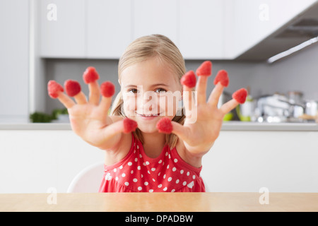 Girl putting raspberries on fingers - Stock Photo