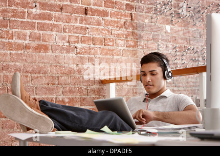 Young man using digital tablet wearing headphones, feet up - Stock Photo