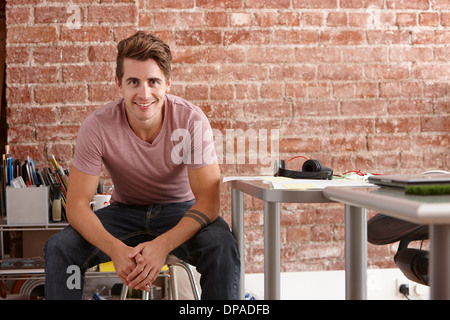 Portrait of young man sitting on chair in creative office - Stock Photo