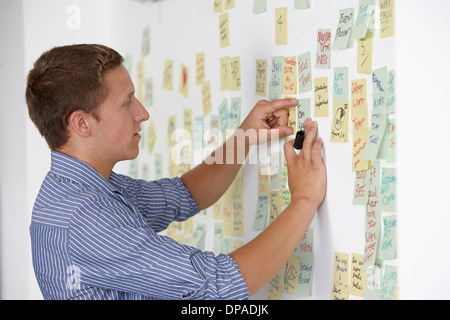 Young man sticking adhesive note on wall - Stock Photo