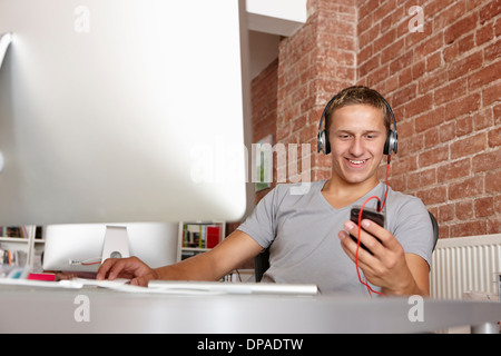 Young man at work using mp3 player - Stock Photo