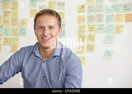 Portrait of young man with adhesive notes in background