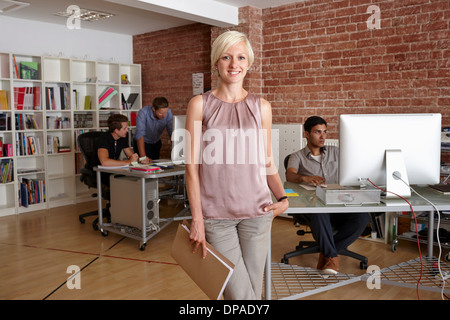 Portrait of mid adult woman in creative office - Stock Photo