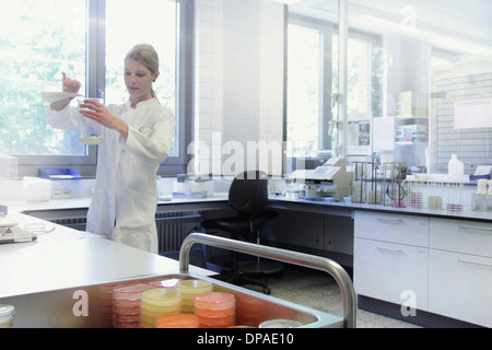 Scientist mixing liquids in beakers - Stock Photo