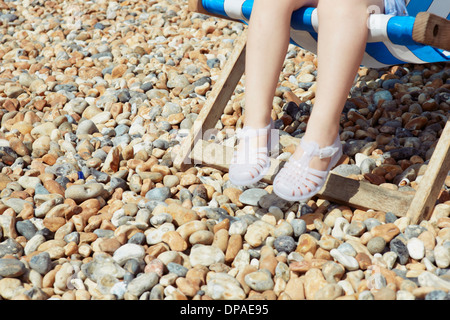 Child with plastic sandals on beach deck chair - Stock Photo
