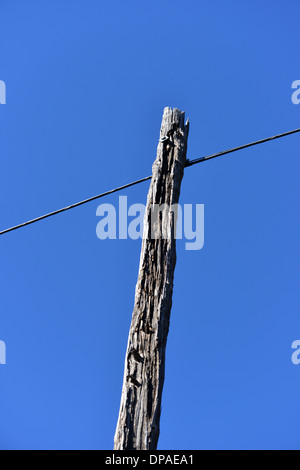 Old telegraph pole with wire strung across, stark against a deep blue sky. America - Stock Photo