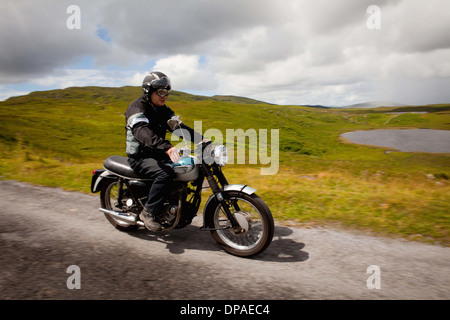 Senior male on motorbike on rural road - Stock Photo