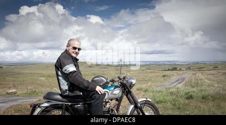 Senior male motorcyclist taking a break - Stock Photo