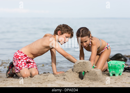 Brother and sister on beach building sandcastle - Stock Photo