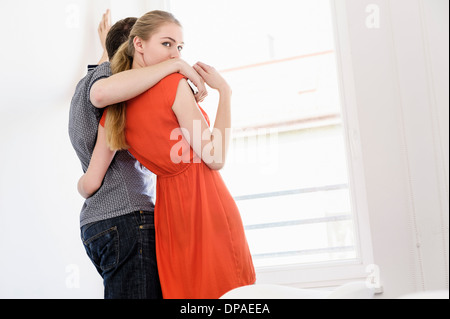 Young couple in front of window - Stock Photo