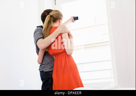Young couple taking photograph from window - Stock Photo