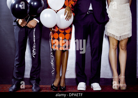 Waist down shot of group of friends with balloons - Stock Photo