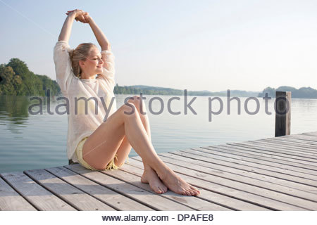 Young woman relaxing on lake pier - Stock Photo