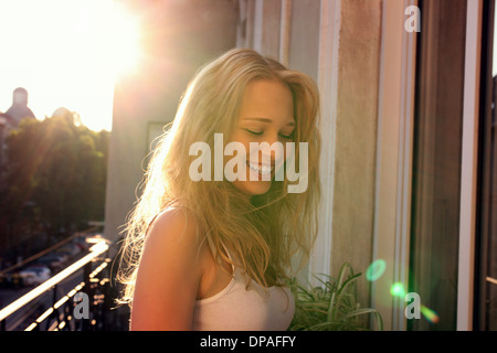 Young woman standing on city apartment balcony - Stock Photo