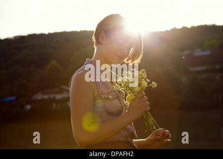 Young woman in meadow holding bunch of wild flowers - Stock Photo